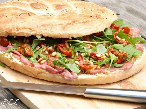 Belegd Turks brood met rosbief, rucola, zongedroogde tomaten, pijnboompitten en kruidenboter. Ideaal als je voor een gezelschap brood moet smeren, voor feestjes of een picknick!
