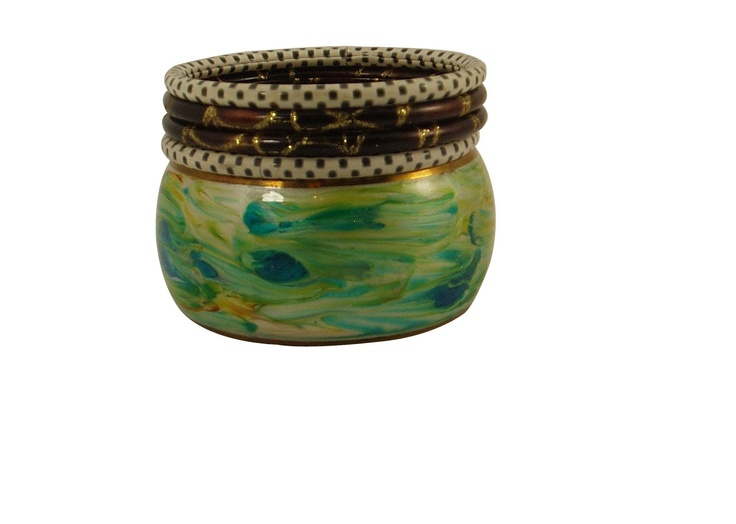 This is a set of 5 bangles. The bold wide bangle is hand painted in pastel shades of blue and sea green and has gold tone border. This set also has a pair of white bangles with delicate tiny black polka dots and a pair of rich chocolate brown bangles with gold color vine pattern all around giving it a rich look. http://www.banglehut.com