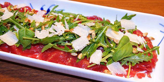 Super nem opskrift på carpaccio, der smager helt fantastisk med rucola, parmesan og ristede pinjekerner på toppen.