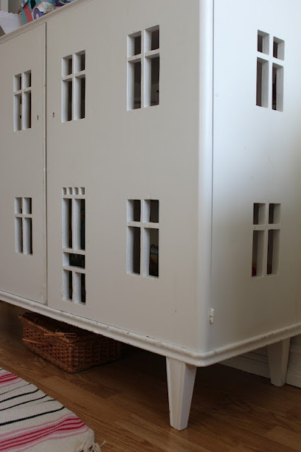 cut-out windows and door in a cabinet to make a dollhouse