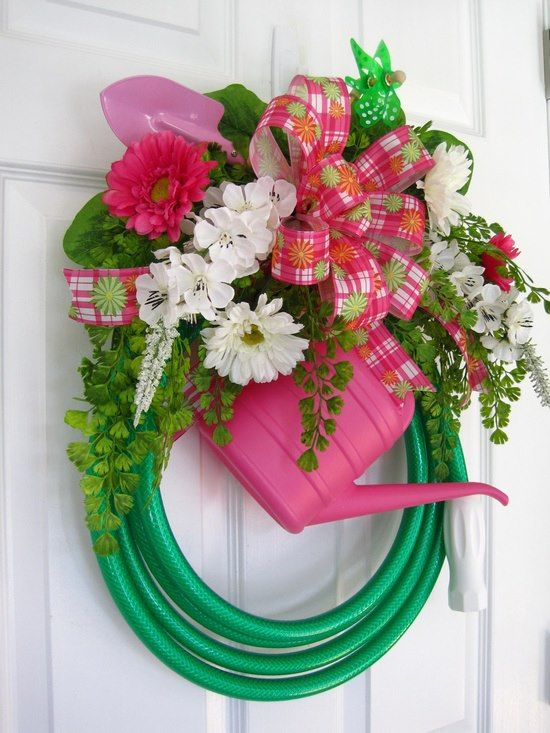 Door wreath made with piece of garden hose and watering can.  Too cute! Perfect for the hose my Dog chewed up!!