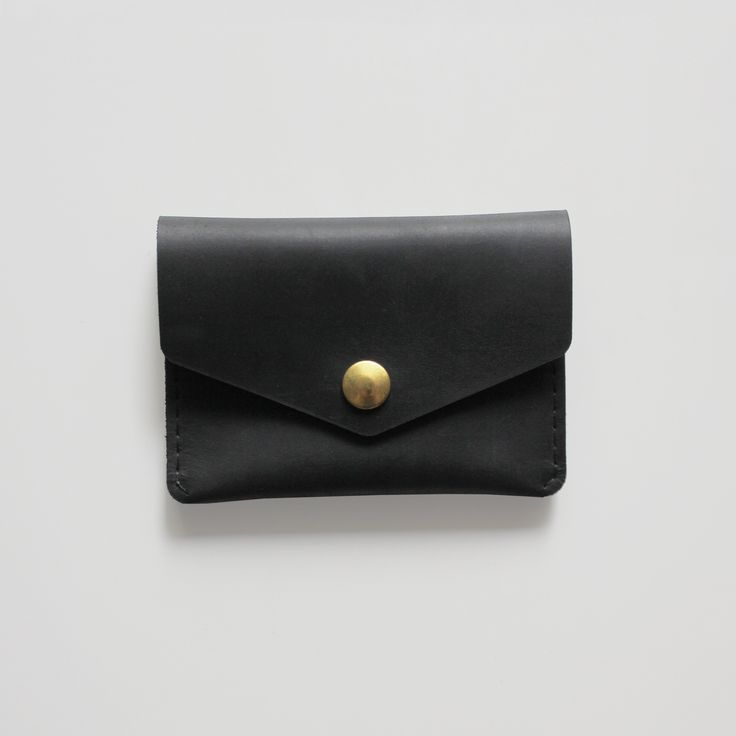 "Built and designed for your essentials, this hand stitched wallet is secured with a brass button and fits comfortably in your pocket.Handcrafted in Toronto, Canada.Black Stone OiledSize: 4.25"" x 3.125"