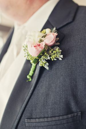 Groom with pink and green boutonniere pinned to his dark gray suit @myweddingdotcom