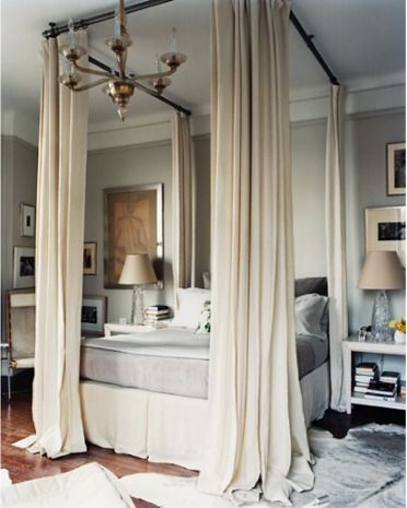 Curtain rods hung from the ceiling to simulate a canopy bed which