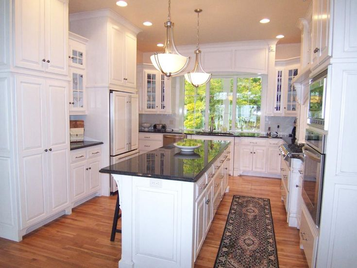 This traditional all-white kitchen with light hardwood flooring,features a granite-topped kitchen island, gorgeous pendant lighting, and spectacular window allowing for natural light to flood the space.