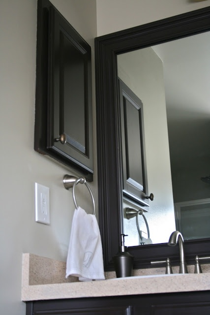 Framed Bathroom Mirror This is awesome!! I am going to do this to all my cabinets and countertops.