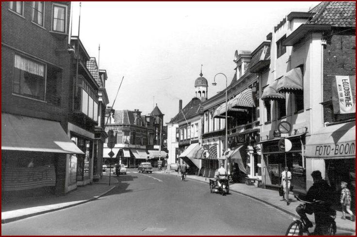 Bron: ToenWasAlmeloNogMooi.nl  Grotestraat Zuid met geheel rechts nog Foto Boom en links na het aanliggende pand boekhandel Hilarius de Jong. Aan het het oude verkeershuis met links ervan Pezie mode.