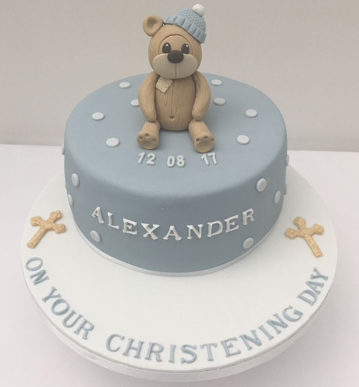 Christening cake with teddy bear wearing woolly hat.  Blue and white text with gold  cross.  The Cake Lab Bakery, Ranelagh, Dublin, Ireland. Artisan Baking Studio.