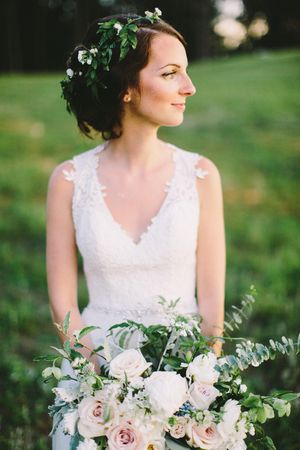 Bride's bouquet- bohemian inspired with eucalyptus, cream and white roses, tweedia,blue thistle, and other soft romantic flowers with a loose floral crown of jasmine vine with small white flowers.  Cream & Dusty Blue Summer Real Wedding — Flowers by Petal Flower Company, photo by Tyler Phenes.