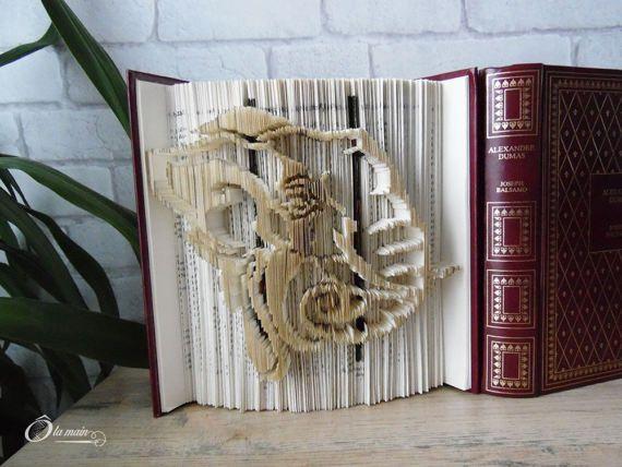 La collection A Livre Ouvert est une série de livres doccasion transformés en objets de décoration via plusieurs techniques (découpage, pliage ou décou-pliage). Chaque page est découpée et/ou pliée à la main pour donner vie à un motif.  Le modèle Pachiderme est un livre découplié représentant une tête déléphant. Le livre mesure 20 cm de haut et possède une magnifique couverture bordeaux agrémentéde motifs vert et or. VENDU SEUL