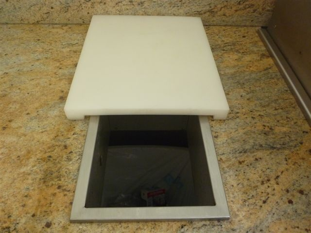 Stainless steel lid removed and the chopping board slides back to allow access to a rubbish bin installed beneath or a small in bench tub. BKCB