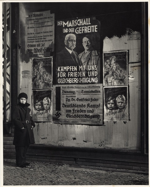 Roman Vishniac's daughter, Mara, posing in front of an election poster for Hindenburg and Hitler, Berlin, 1933. © Mara Vishniac Kohn, courtesy International Center of Photography.