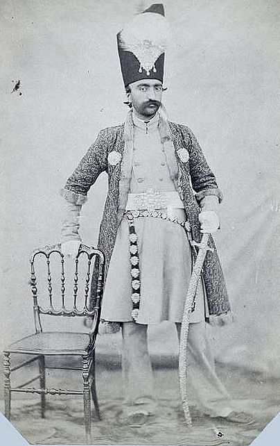 Portrait of Nasir al Din Shah, King of Iran from 17 September 1848 to 1 May 1896 when he was assassinated.1852 by luigi Pesce. In this formal portrait he wears a costume of European-style coat and trousers with a Persian robe, a long sword hangs from his belt. These attributes accentuate both his cultural sophistication and military prowess. The practice of photography was taken up in Iran soon after its invention in Europe, and Nasir al-Din Shah was an enthusiastic amateur himself.