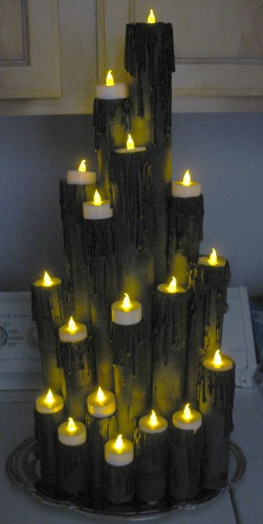 A spooky candle display without any fire danger: Wrapping paper tubes, paper towel tubes and TP tubes, hot glue for the 'drips', all painted with a flat black spray paint, and battery operated tea lights.