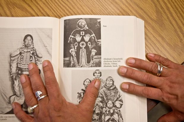 """Salome Awa displays an archival image from the book """"Northern Voices"""" showing her great grandfather shaman Ava in his sacred caribou skin parka. Abraham and his family happens to appear on the page as well. (Kieran Oudshoorn/CBC)"""