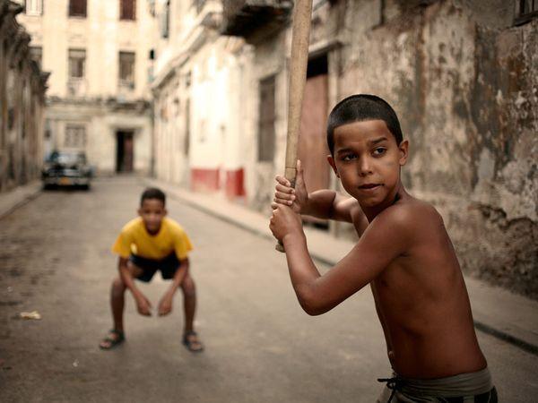 Jongens spelen honkbal (de nationale sport van Cuba) in de straten van Havana