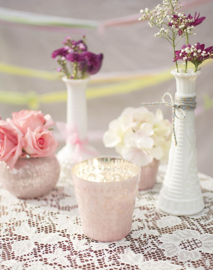 Detail your spring wedding in dreamy pastel tones! Place pink mercury glass bud vases and candle holders alongside milk glass accents and complete the look with lace, tea light candles and flowers.