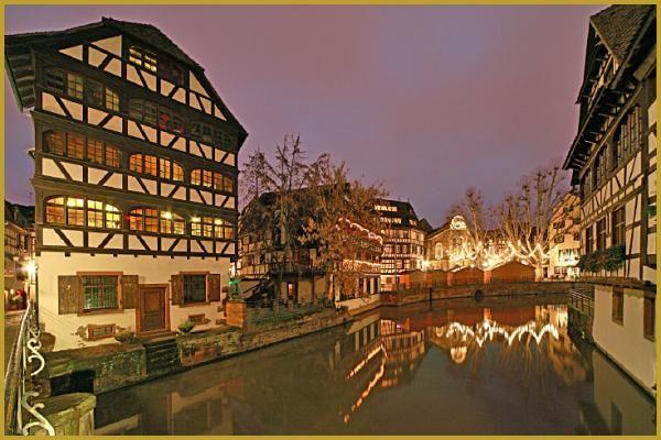 Photo du pont tournant du canal de navigation à la Petite France dans les lumières de Noël illuminant les maisons alsaciennes à colombages et la place Binjamin-Zix avec son marché de Noël. Alsace photos, Noël en Alsace Strabourg.