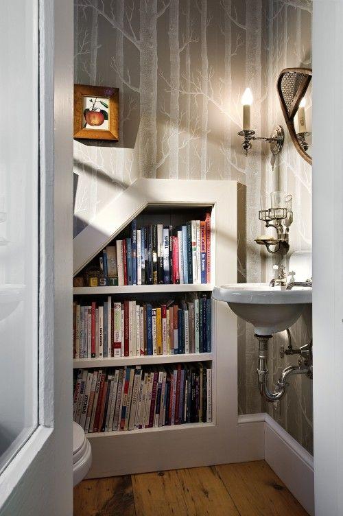 I love this half bath!  The wallpaper + brilliant way to incorporate reading material into the decor