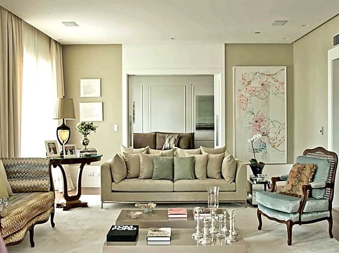 feminine living room in shades of pale putty...notice the abstract art, flamestitch sofa & collection of ornate silver candlesticks