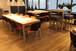 Sfeervolle kantine met hoge tafels met barkrukken en lage tafels met kantinestoelen.