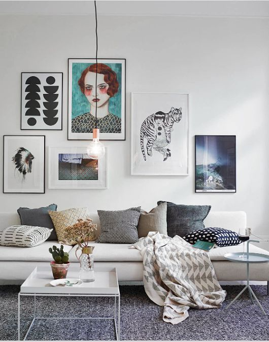 Lightbulb pendant lighting, patterned throw, pillows, and rug. Industrial/modern base furniture and frames, all white and black.