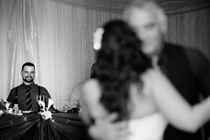 This loving groom admiring his gorgeous bride while she dances with her dad.