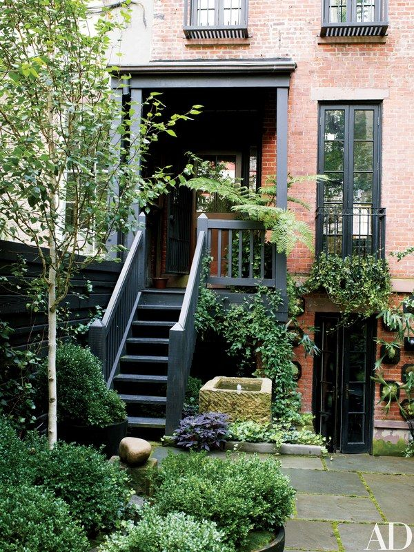 The painted trim of the 1905 house is complemented by matte-black accents found throughout the garden | archdigest.com