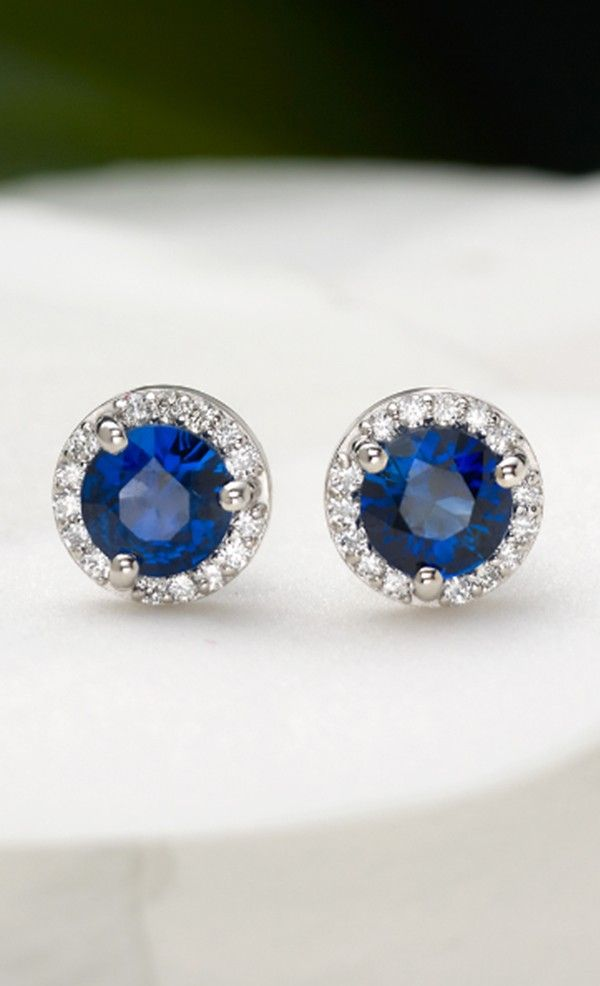 These mesmerizing earrings feature richly hued deep blue sapphire centers sur