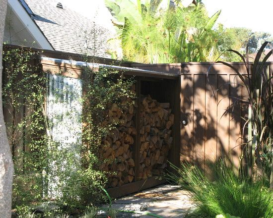 NOT a bottle wall, but makes the firewood stash look like a wall, and the wood is safe from the elements.  (Do wonder about termites with the wood up next to the outside wall and foundation.)