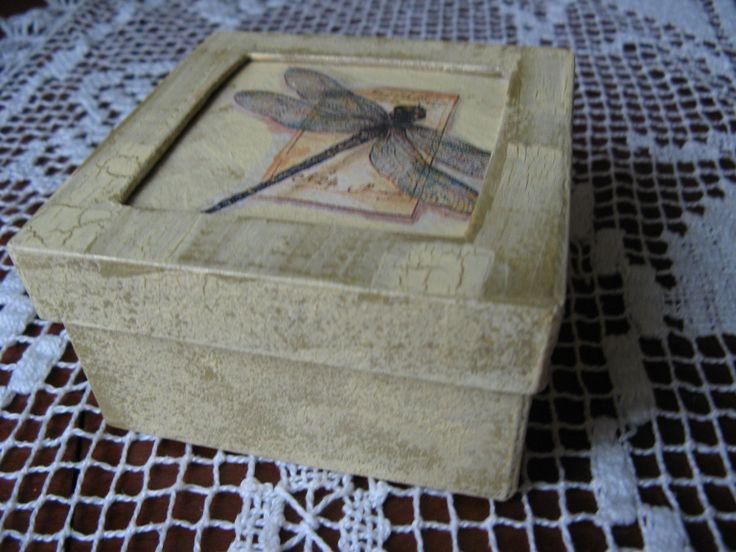 Pudełko z dykty ręcznie malowane i zdobione. Odcienie ecru i złotego efektownie wykończone ważką na wieczku. Wymiary 10x10x10cm.