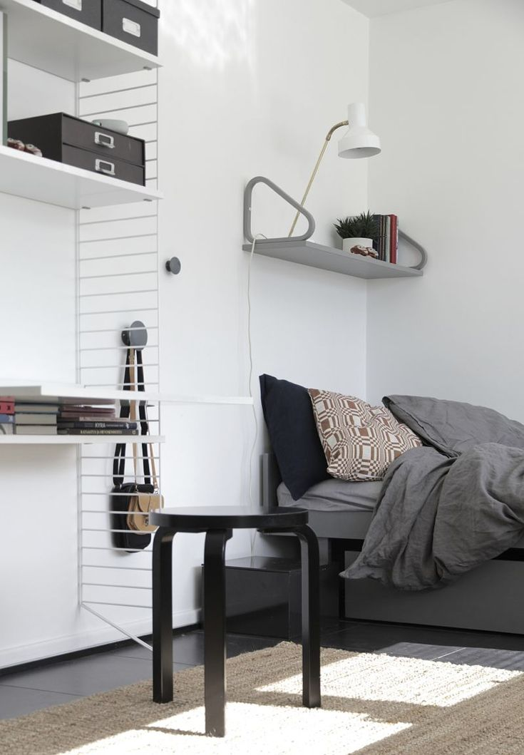 White String shelf, grey wall shelf and black stool from Artek. Via Decordots.