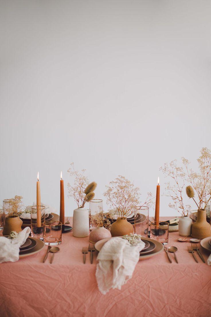 Tons blush et fleurs neutres avec bougies taupe sur ce décor de table