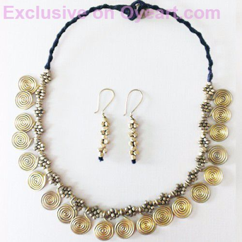 This traditional dhokra necklace has been made with handmade spiral coins and beads in villages of Orissa. The necklace is 18 inches long and has 20 brass spiral coins (diameter 1.25cm approx.) arranged beautifully with golden beads in a black thread. The necklace comes with a set of matching earrings to glam up your appearance.
