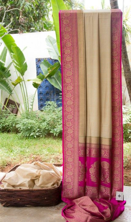 This Benares silk is checkered with ivory white and beige. The border and pallu have intricate gold zari work over magenta adding a traditional finish