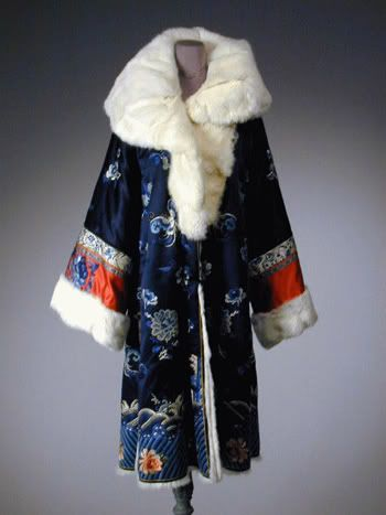 Midnight Blue Fur Lined Embroidered Coat  Chinese, 1920s   Knee length, fashioned with large shawl fur collar and cuffs, with frog closures, side slits, embroidered in blue tones with flowers and traditional wave and mountain border, some Peking knot work.
