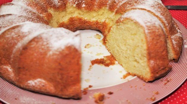 2 xícaras de farinha de trigo  - 1 colher (chá) de fermento em pó  - 1 pitada de sal  - 1 xícara de leite de coco  - ¼ xícara de manteiga sem sal derretida   - 4 ovos grandes, temperatura ambiente  - 2 xícaras de açúcar refinado  - raspas da casca de 1 laranja  - 1 colher (chá) de extrato de baunilha  - 2 colheres (chá) de rum escuro (utilizei Cointreau)  - ¾ xícara de coco em flocos, sem adição de açúcar  - suco de ½ laranja  - açúcar de confeiteiro, para polvilhar