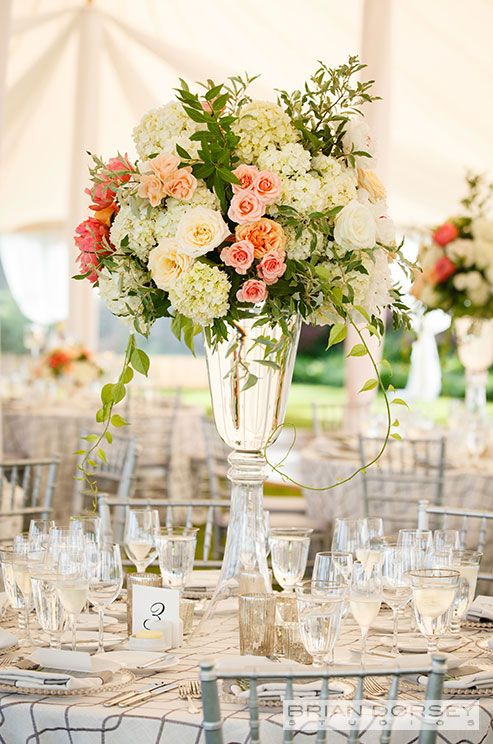 A floral centerpiece of variegated roses and white hydrangeas is complete with a clear vase. love the vase
