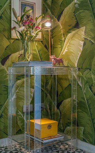 Papel mural tropical exótico con diseño de grandes hojas verdes tropicales de plátano. Sobre la mesa de arrimo, dispusimos una lámpara de cobre y bajo ésta, una caja cofre amarilla lacada. El piso es de patrón geométrico en blanco y negro.