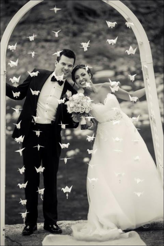 White wedding arch with origami swans. So sweet!