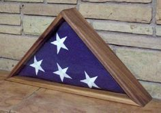 When someone in the United States of America who once served in the armed forces dies, a military honor guard presents a folded American flag to the family at the graveside committal service.  Many people buy or make a wooden three-cornered flag case with a glass front.  Although a cheap flag case can be had for as little as $20 US, a decent case made of solid wood can cost over $100 US.  At this link you can read about the significance of the folds in the flag and ot...