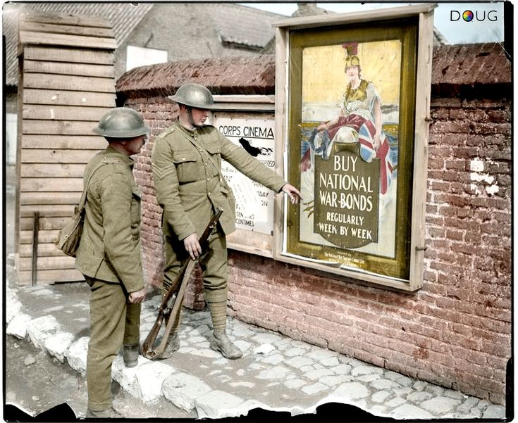 Two British soldiers pose by National War Bonds and Corps Cinema advertisements in Hinges, Pas-de-Calais, France on the 11th April 1918. The illustrated poster of interest, issued by the National War Savings Committee (Salisbury and London) reads 'Buy National War Bonds Regularly Week By Week', while a notice is relating to the opening times and ticket prices for the Corps Cinema.