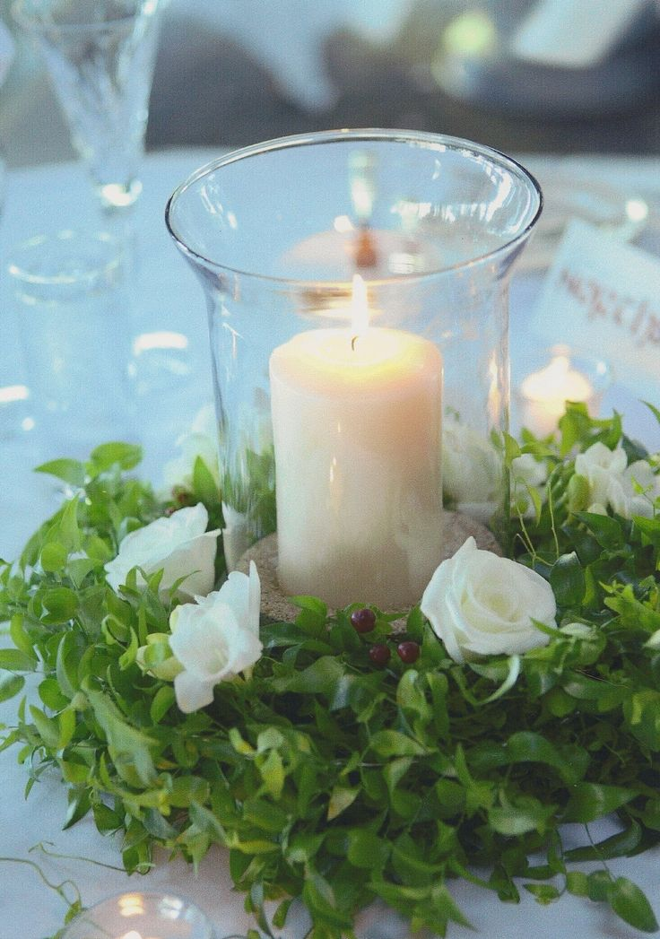 """Hurricane-style arrangement with pillar candle nestled in sand -- surrounded by a loose """"wreath"""" of white Roses, Freesia, and Hypericum in a garland of Smilax - design by Heather Murdock of The Blue Orchid"""