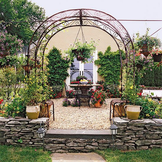 If the view from your backyard faces an ugly shed or garage, think about incorporating it into your garden design. On this narrow lot, the only view was of the homeowner's ugly garage. But with a can of paint and an inexpensive French door, they turned an ugly duckling into a swan. In fact, they were so happy with the transformation, they added a Mediterranean style patio right up against the new garage doors.