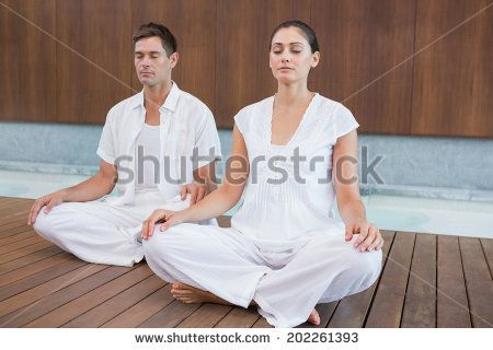 Attractive couple in white sitting in lotus pose in health spa