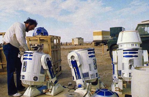 R2-D2 prop being prepared for shooting in the Tunisian Desert. Left R2 is the radio controlled unit where the middle one is the R2 that fits Kenny Baker inside. Notice the tubes going from the body to the legs. Unpacking crates a R2 unit got R5-D4s head.