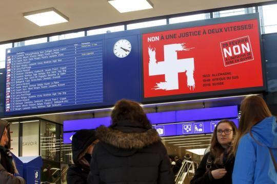 Drastische Werbung gegen die SVP-Initiative in Genf: Das weiße Schweizer Kreuz auf roter Flagge wird zum Hakenkreuz. Im Text: Nein zu einer Justiz der zwei Geschwindigkeiten. Und: 1933 Deutschland, 1948 Südafrika, 2016 Schweiz – Verweise auf faschistische Regime