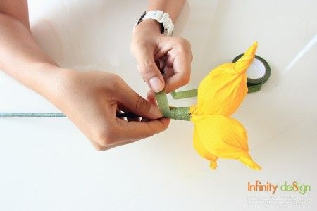 5.นำกลีบดอกไม้ที่ได้จัดเตรียมไว้ มาประกอบให้เป็นช่อ แล้วนำฟลอร่าเทปมาพันลงไปเพื่อยึดติดกับก้าน จะใช้เป็นก้านกระดาษสำเร็จรูปหรือใช้วัสดุอื่นที่เป็นลักษณะก้านยาวก็ย่อมได้