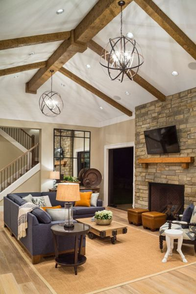 Learn how to properly light any size room with the MAGIC number.  I love the cathedral ceiling in this living room.  The colour palette, wood beams and fireplace are just stunning.  Photo source:  Home Bunch by TTM Development #LivingRoom #CathedralCeiling #LightingIdeas