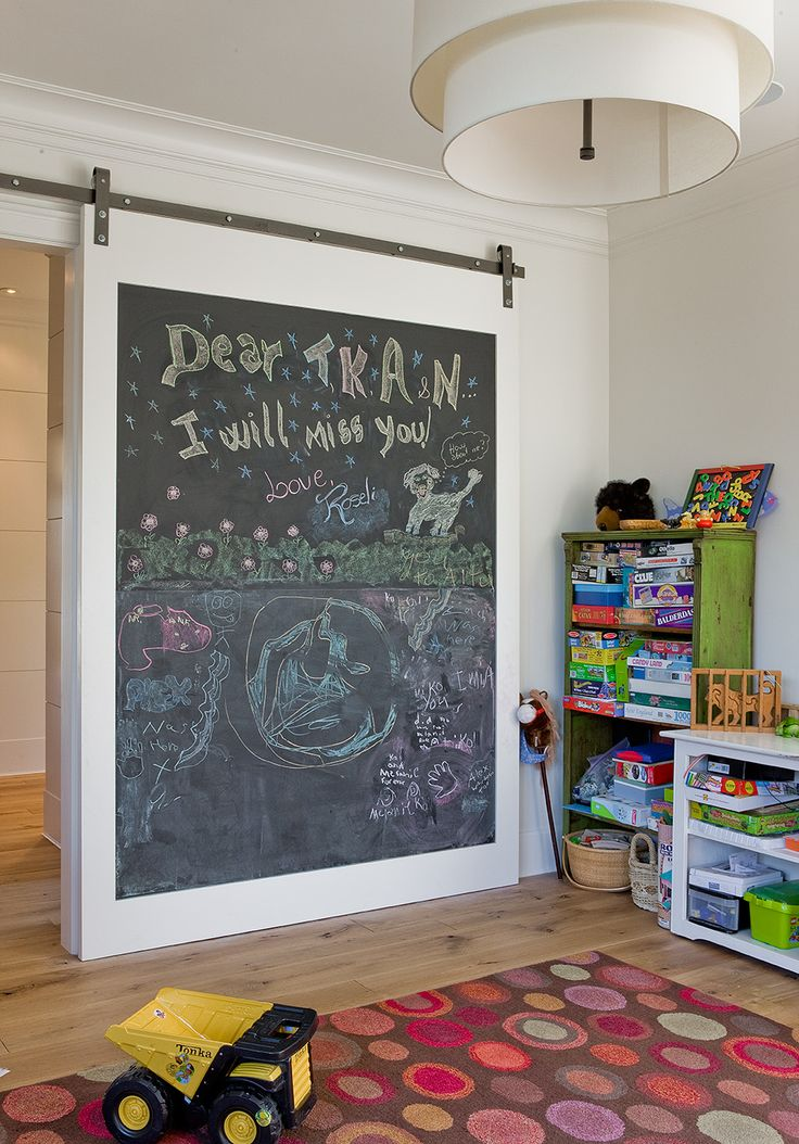 A Chalkboard Barn Door On Rails Slides Open To Reveal Playroom Filled With  Distressed Green Bookcases Stacked On Top Of Each Other Beside A Low White  ...